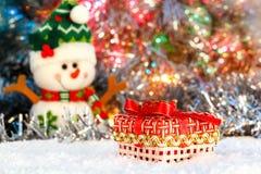 Rotes Weihnachtsgeschenk steht auf dem Schnee gegen den Hintergrund einen fröhlichen Schneemann und ein glänzendes Lametta Glühen Lizenzfreies Stockbild