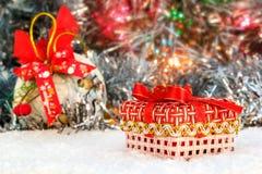 Rotes Weihnachtsgeschenk steht auf dem Schnee gegen einen Hintergrund eines Weihnachtsballs und des glänzenden Lamettas Glühende  Lizenzfreie Stockbilder