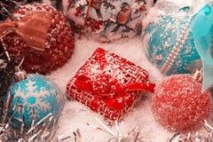 Rotes Weihnachtsgeschenk steht auf dem Schnee gegen einen Hintergrund von Weihnachtsbällen und von glänzendem Lametta Lizenzfreies Stockfoto