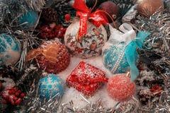 Rotes Weihnachtsgeschenk steht auf dem Schnee gegen einen Hintergrund von Weihnachtsbällen und von glänzendem Lametta Stockbilder