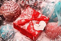 Rotes Weihnachtsgeschenk steht auf dem Schnee gegen einen Hintergrund von Weihnachtsbällen und von glänzendem Lametta Stockfotografie
