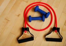 Rotes Widerstand-Band und blaue Gewichte auf Gymnastik-Fußboden Lizenzfreie Stockbilder