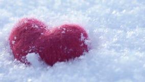 Rotes woolen Herz auf dem Lügen auf dem weißen klaren Schnee im Winter stock video