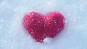 Rotes woolen Herz auf dem Lügen auf dem weißen klaren Schnee im Winter stock video footage