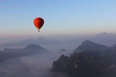 Rotglühendes Heißluftballonfloss über Misty Mountain in Vang Vieng, Lao stockbild