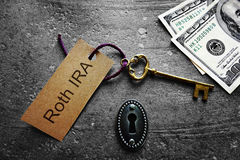Roth IRA Key tag and cash. Gold key with Roth IRA tag, with keyhole and cash Royalty Free Stock Photo