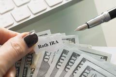 Roth IRA konto för individuell avgång, plan med kassa oss dollar på en tabell fotografering för bildbyråer
