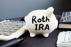 Roth IRA op een spaarvarken wordt geschreven dat Pensioneringsplan stock foto