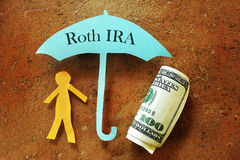 Roth IRA. Paper cutout person under a Roth IRA umbrella Royalty Free Stock Photos