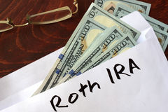 Roth IRA som är skriftlig på ett kuvert med dollar Arkivbild