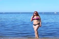 Rothaarig plus die Größenfrau, die auf Küste stillsteht Lizenzfreie Stockfotos