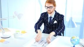 Rothaarige-Architekturingenieur Opening Blueprint auf Schreibtisch im Büro Lizenzfreie Stockfotos