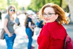 Rothaarige Frau in der roten Bluse mit den Gläsern, die zurück schauen stockfoto