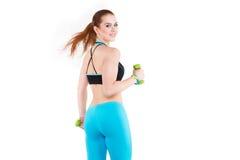 Rothaarige Frau in der Sportkleidung, die Übung mit Dummköpfen tut Lizenzfreie Stockfotografie