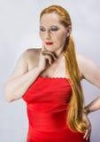 Rothaarige Frau des Porträts in einem roten Kleid Lizenzfreie Stockfotografie