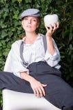Rothaarige Frau mit Kappe im Garten bietet Apfel an Stockfotografie