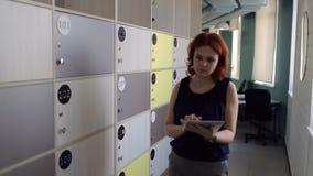 Rothaarige Geschäftsfrau, die zur Halle innerhalb des Büros geht stock footage