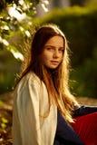 Rothaarige 12 Jahre alte Mädchen, die auf einem Felsen und einem beschäftigten Denken sitzen Lizenzfreies Stockfoto