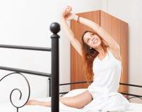 Rothaarige junge Frau wacht in ihrem Bett auf Stockfoto