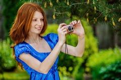 Rothaarige lächelnde junge Frau fotografiert Lizenzfreies Stockfoto