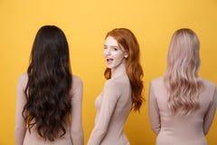 Rothaarigedame, die nahe den blonden und Brunettefrauen blinzelt Stockbild