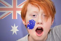 Rothaarigefanjunge mit der australischen Flagge gemalt auf seinem Gesicht Lizenzfreies Stockbild