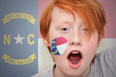 Rothaarigefanjunge mit der Nord-Carolinastaatsflagge gemalt auf seinem Gesicht Stockfoto