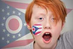 Rothaarigefanjunge mit der Ohio-Staatsflagge gemalt auf seinem Gesicht Stockfotos