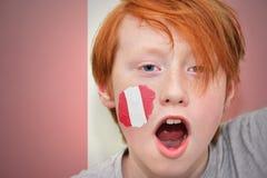 Rothaarigefanjunge mit der peruanischen Flagge gemalt auf seinem Gesicht Stockfoto