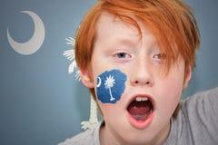 Rothaarigefanjunge mit der South- Carolinastaatsflagge gemalt auf seinem Gesicht Stockfotografie