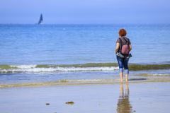 Rothaarigefrau auf der Küste stockfotos