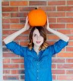 Rothaarigefrau in den Jeans kleidet das Halten des orange Herbstkürbises Lizenzfreie Stockbilder