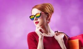 Rothaarigefrau in der Sonnenbrille mit Regenbogen und mit Einkaufstaschen lizenzfreie stockfotos