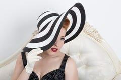 Rothaarigefrau, die einen gestreiften Hut hält stockfotos