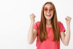 Rothaarigefrau, die für Freund bei der Ausführung am Stadium hoch anhebt Fäuste in der unterstützenden Bewegung froh lächelt zuju lizenzfreies stockfoto