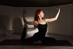 Rothaarigefrau, die hatha Yoga ausübt lizenzfreies stockfoto