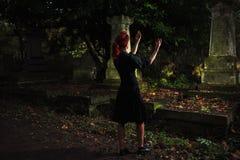 Rothaarigefrau, die Ritual am Grab durchführt Stockfotografie