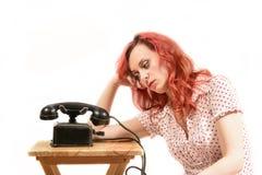 Rothaarigefrau mit einem Retro- Blick, der auf das Telefon wartet Stockfotografie