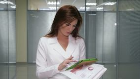 Rothaarigegeschäftsfrau in der Klage mit Tablette und Dokument, das in der Halle des Büros steht stock video