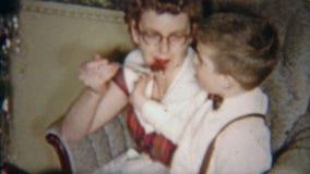 1954: Rothaarigeglasmädchen, das Kuchen isst und Kleinkind anbietet NEWARK, NEW-JERSEY stock footage