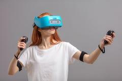 Rothaarigemädchen, das VR-Gläser lokalisiert über Weiß verwendet Erfahrung der virtuellen Realität lizenzfreies stockbild