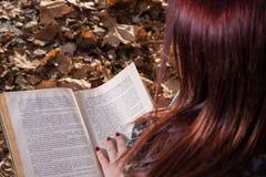Rothaarigemädchen, das auf Bank im Park- und Lesebuch sitzt Lizenzfreie Stockfotografie