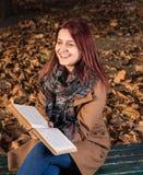 Rothaarigemädchen, das auf Bank im Park- und Lesebuch sitzt Stockbild