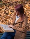 Rothaarigemädchen, das auf Bank im Park- und Lesebuch sitzt Lizenzfreie Stockbilder
