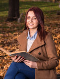 Rothaarigemädchen, das auf Bank im Park- und Lesebuch sitzt Lizenzfreies Stockbild