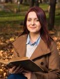 Rothaarigemädchen, das auf Bank im Park- und Lesebuch sitzt Stockfotos