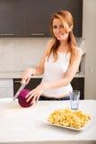 Rothaarigemädchen, das in der Küche schneidet Stockbild
