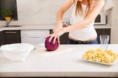 Rothaarigemädchen, das in der Küche schneidet stockbilder