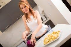 Rothaarigemädchen, das in der Küche schneidet stockfotografie