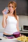 Rothaarigemädchen, das in der Küche trinkt lizenzfreie stockfotos